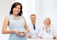 Femme enceinte heureuse faisant le geste de coeur sur le ventre Photographie stock libre de droits