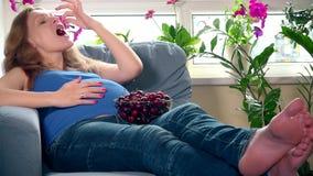 Femme enceinte heureuse mangeant la baie de cerise regardant l'appareil-photo et le sourire clips vidéos