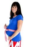 Femme enceinte heureuse montrant son ventre avec un arc rose Images stock