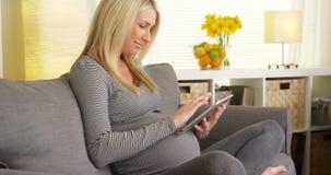 Femme enceinte heureuse s'asseyant sur le divan utilisant le comprimé Photographie stock