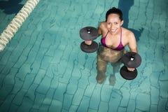 Femme enceinte heureuse s'exerçant dans la piscine avec des poids Images libres de droits