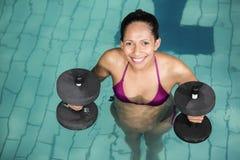 Femme enceinte heureuse s'exerçant dans la piscine avec des poids Image libre de droits