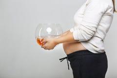 Femme enceinte heureuse tenant un bocal à poissons avec un poisson rouge dans son h Photos stock