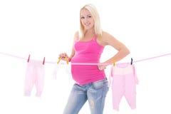 Femme enceinte heureuse traînant des vêtements d'enfant d'isolement sur le blanc Image stock