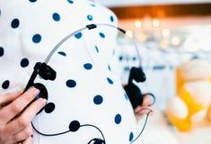 Femme enceinte jouant la musique pour le bébé par les écouteurs Photos stock