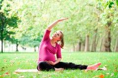 Femme enceinte jouant le yoga chez Hyde Park, Londres photographie stock libre de droits