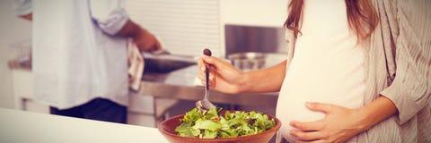 Femme enceinte mélangeant une salade dans la cuisine images libres de droits