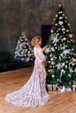 Femme enceinte magnifique avec les cheveux ordonnés étonnants blonds, portant une robe légère translucide de dentelle blanche ave images stock