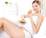 Femme enceinte mangeant des fruits frais images libres de droits