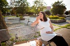Femme enceinte mangeant la tranche de pizza Tir urbain Images libres de droits