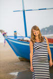 Femme enceinte marchant le long d'une plage Photo stock