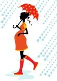 Femme enceinte marchant sous la pluie Photographie stock libre de droits