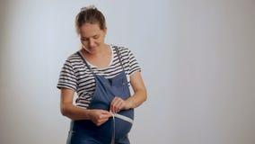 Femme enceinte mesurant son ventre tout en se tenant sur un fond blanc banque de vidéos