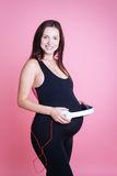 Femme enceinte mettant des écouteurs sur son ventre image libre de droits