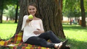 Femme enceinte montrant la pomme dans le parc, le concept de la consommation saine et le mode de vie banque de vidéos