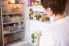 Femme enceinte ouvrant le réfrigérateur image stock