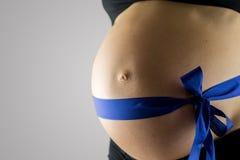 Femme enceinte portant un ruban bleu Photographie stock