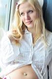 Femme enceinte près de l'hublot Image libre de droits