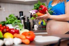Femme enceinte préparant un repas sain dans la cuisine Photos libres de droits