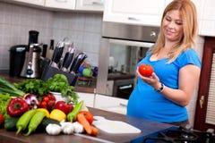 Femme enceinte préparant un repas sain dans la cuisine Photographie stock libre de droits
