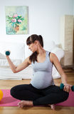 Femme enceinte pratiquant à la maison image stock