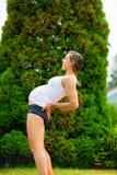 Femme enceinte pratiquant la demi pose de roue en parc images libres de droits