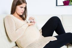 Femme enceinte prenant des pilules Image libre de droits