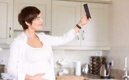 Femme enceinte prenant un selfie Image stock