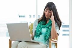 Femme enceinte réfléchie à l'aide de l'ordinateur portable image stock