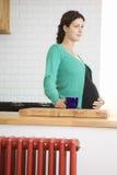 Femme enceinte réfléchie avec la tasse de thé Photos libres de droits