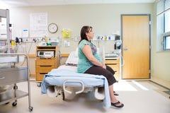 Femme enceinte réfléchie s'asseyant sur le lit d'hôpital Photos stock