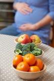 Femme enceinte regardant des bols de fruits et légumes sains Photo stock
