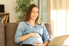 Femme enceinte regardant l'appareil-photo à la maison Photographie stock