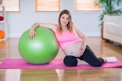 Femme enceinte regardant l'appareil-photo avec la boule d'exercice Photo libre de droits