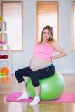 Femme enceinte regardant l'appareil-photo se reposant sur la boule d'exercice Photos stock