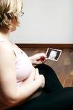Femme enceinte regardant l'image d'ultrason photographie stock libre de droits