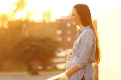 Femme enceinte regardant loin dans un balcon photos libres de droits