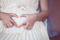 Femme enceinte reposant et faisant la forme de coeur de main Images libres de droits