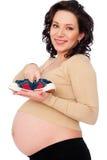 Femme enceinte retenant de petites espadrilles Images libres de droits