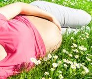 Femme enceinte s'étendant sur l'herbe Image libre de droits