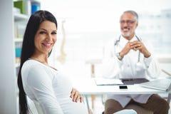 Femme enceinte s'asseyant à la clinique pour le contrôle de santé Photo stock