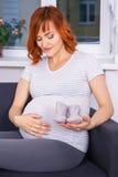 Femme enceinte s'asseyant avec des articles d'habillement pour le bébé nouveau-né Photo libre de droits