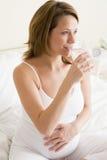 Femme enceinte s'asseyant dans la chambre à coucher avec la glace Images stock