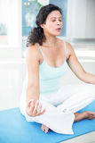 Femme enceinte s'asseyant dans la pose de lotus avec des yeux fermés Images stock