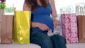 Femme enceinte s'asseyant entre les paniers et frottant son grand ventre banque de vidéos