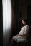 Femme enceinte s'asseyant près d'une fenêtre photos libres de droits
