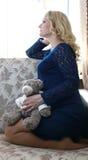 Femme enceinte s'asseyant sur le divan photographie stock libre de droits