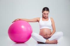 Femme enceinte s'asseyant sur le plancher avec la boule de forme physique Image stock