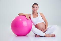 Femme enceinte s'asseyant sur le plancher avec la boule de forme physique Photographie stock libre de droits