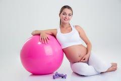 Femme enceinte s'asseyant sur le plancher avec la boule de forme physique Photographie stock